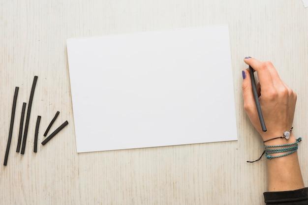 De hand die van de vrouw natuurlijke houtskoolstok met leeg witboek op houten achtergrond houdt