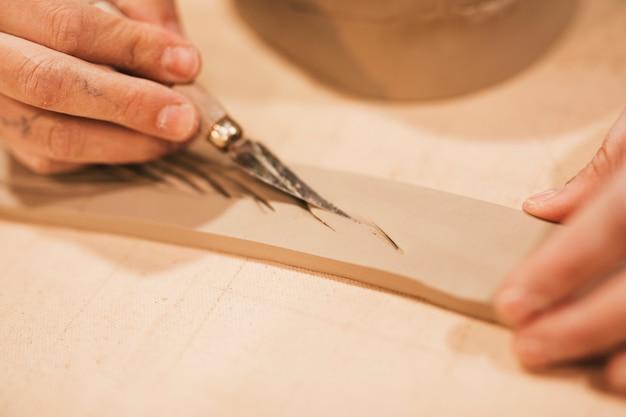De hand die van de vrouw op de natte rechthoekige vorm met hulpmiddelen snijdt