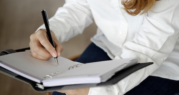 De hand die van de vrouw op leeg notitieboekje op bureau schrijft