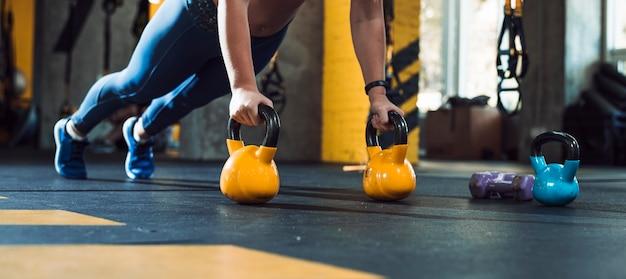 De hand die van de vrouw opdrukoefeningen op ketelbal doet in gymnastiek