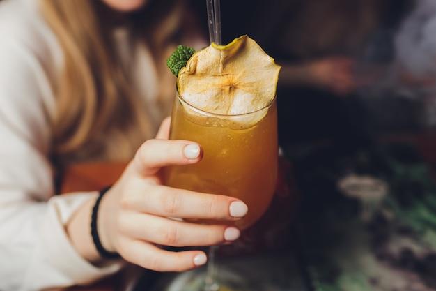 De hand die van de vrouw ouderwets glas met koude cocktail houden tegen vage nachtclubachtergrond.