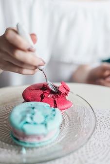 De hand die van de vrouw roomijssandwich met vork op glas transparante plaat eet