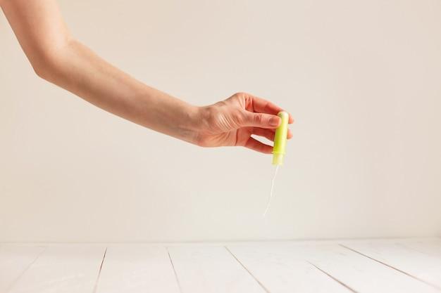 De hand die van de vrouw schone groene katoenen tampon houdt.