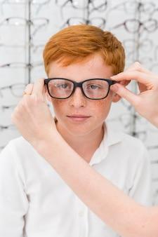 De hand die van de vrouw schouwspel draagt aan jongen in opticawinkel