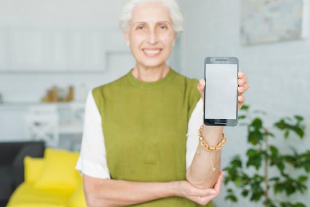 De hand die van de vrouw smartphone met het lege vertoningsscherm toont