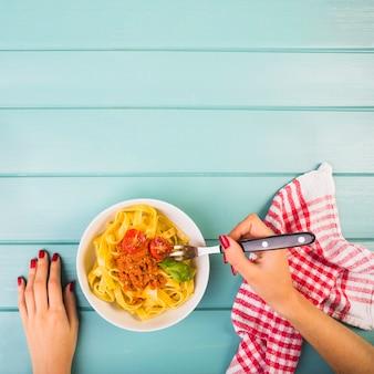 De hand die van de vrouw tagliatelledeegwaren met vork eet