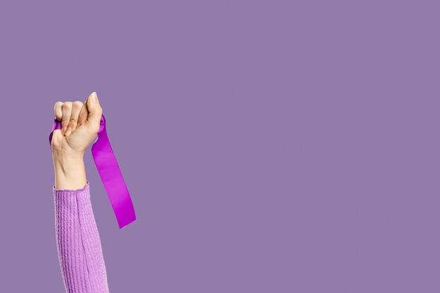 De hand die van de vrouw violet lint en exemplaarruimte houdt