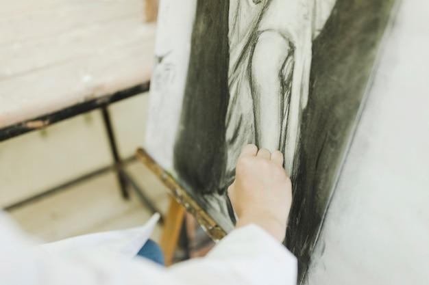 De hand die van de vrouw wijfje op canvas schetst