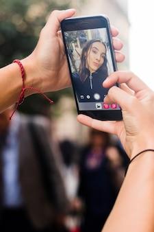 De hand die van de vrouw zelfportret met slimme telefoon neemt