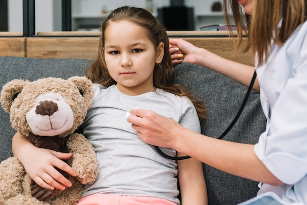 De hand die van de vrouwelijke arts de zwangere teddybeer van de meisjesholding met stethoscoop onderzoekt