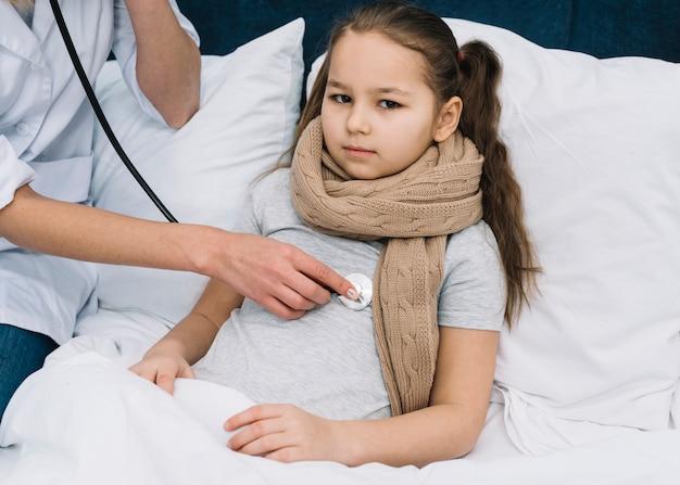 De hand die van de vrouwelijke arts meisje onderzoekt dat op bed met stethoscoop ligt
