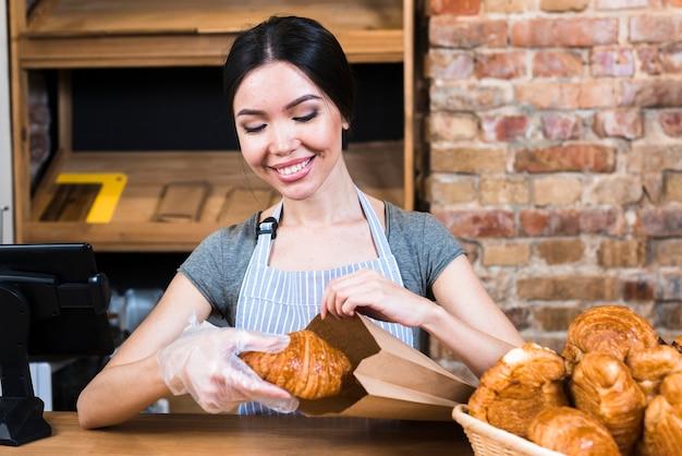 De hand die van de vrouwelijke bakker handschoen draagt die gebakken croissant in document zak verpakt