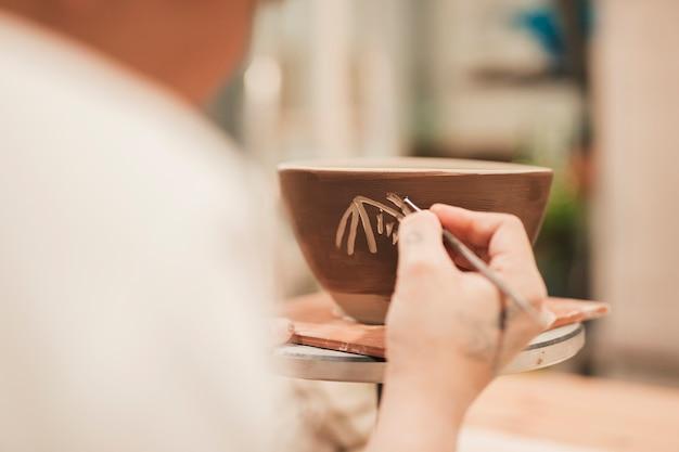 De hand die van de vrouwelijke pottenbakker de kleikom met hulpmiddel verfraait