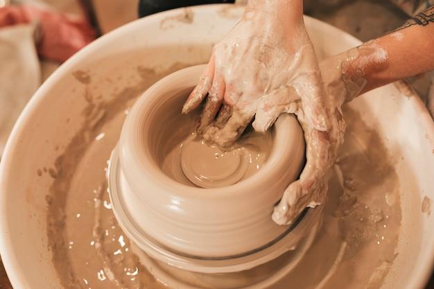 De hand die van de vuile vrouwelijke pottenbakker klei op het wiel van een pottenbakker modelleren