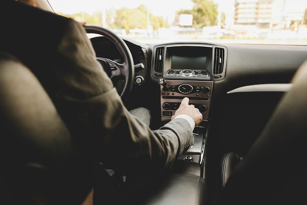 De hand die van de zakenman de toestelpens in auto verschuift