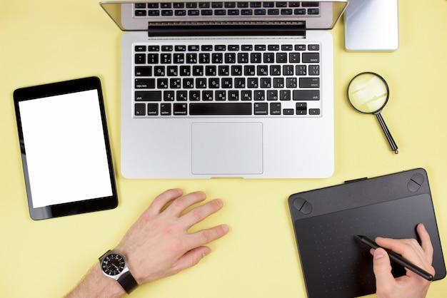 De hand die van de zakenman grafische digitale tablet met laptop en digitale tablet op gele achtergrond gebruikt