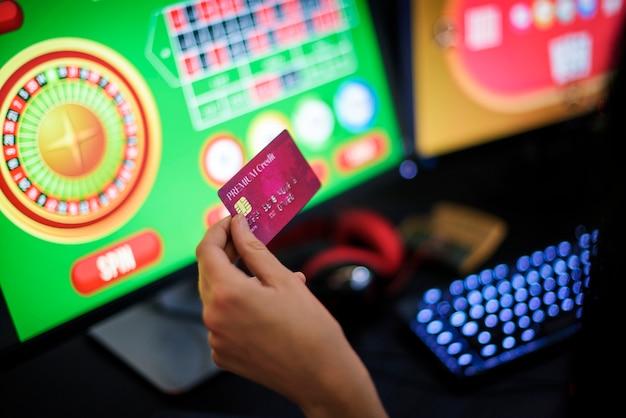 De hand die van een gokker het creditcard spelen houdt