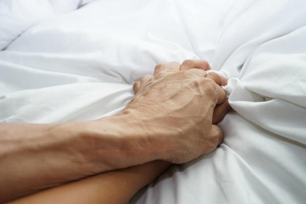 De hand die van een harige man een vrouwenhand voor concept verkrachting en seksueel misbruik houdt