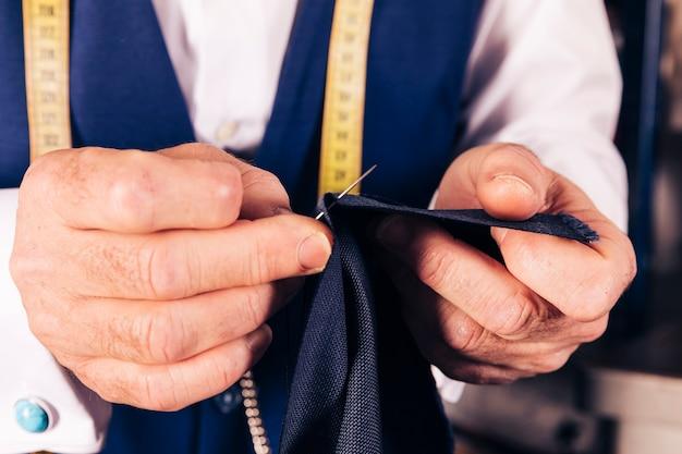 De hand die van een mannelijke kleermaker de stof met naald naaien