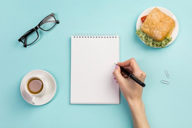 De hand die van een onderneemster op spiraalvormige blocnote met koffiekop en sandwich op het bureau schrijft