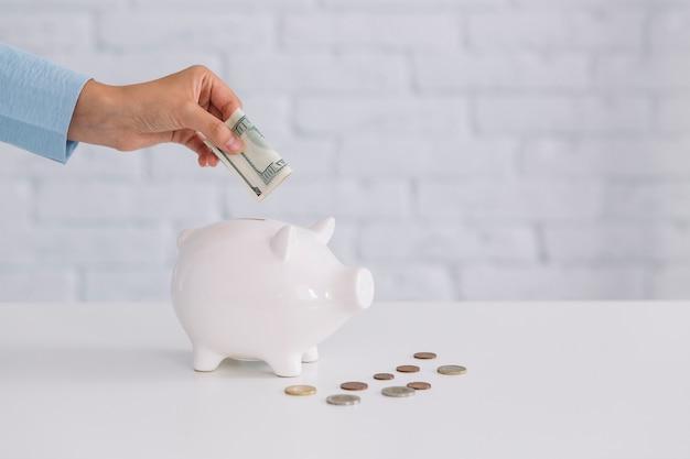 De hand die van een persoon bankbiljet in witte piggybank op bureau opneemt
