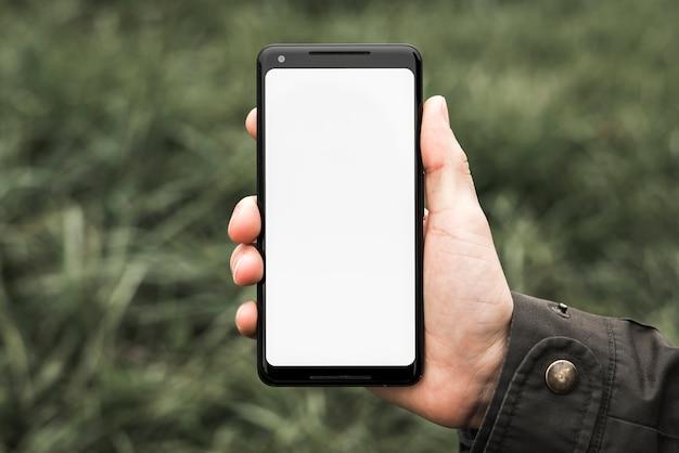 De hand die van een persoon celtelefoon met het witte lege scherm toont