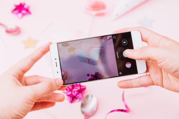 De hand die van een persoon foto van verjaardagsviering op smartphone vangt