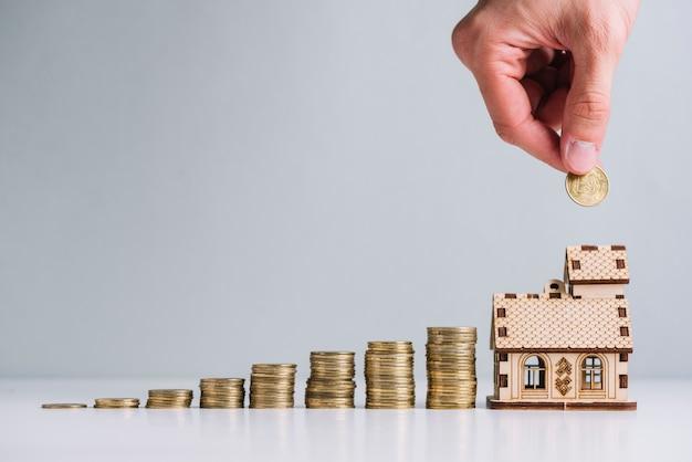De hand die van een persoon geld in het kopen van huis investeert