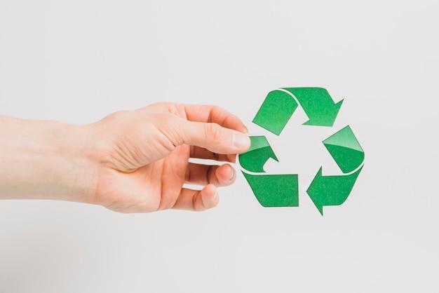 De hand die van een persoon groen kringloopdiepictogram houdt op witte achtergrond wordt geïsoleerd