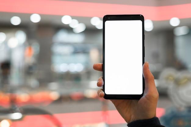 De hand die van een persoon het mobiele scherm toont tegen vage achtergrond