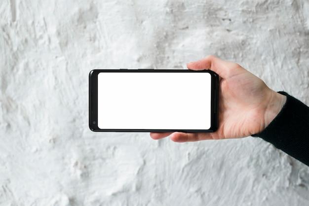De hand die van een persoon het schermvertoning van de mobiele telefoon tegen witte concrete muur toont