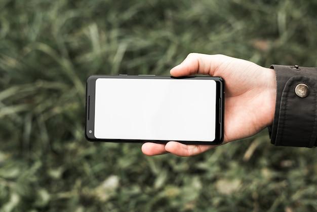De hand die van een persoon mobiele telefoon houdt die witte lege het schermvertoning toont in openlucht