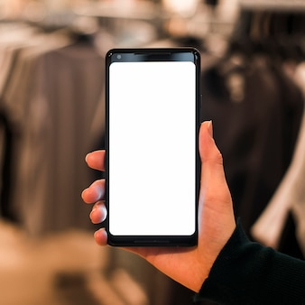 De hand die van een persoon mobiele telefoon in de klerenopslag houdt