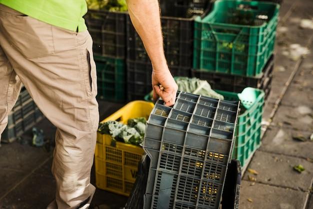 De hand die van een persoon plastic krat bij supermarkt houdt