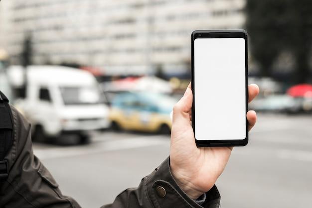 De hand die van een persoon slimme telefoon houden die het witte lege scherm tonen tegen vage weg