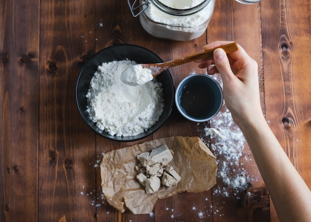 De hand die van een vrouw bloem toevoegt om zuurdesem te maken. bakkerij concept.