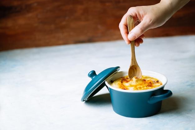 De hand die van een vrouw een houten lepel houdt om een heerlijke hummus met olijfolie en paprika te eten zette op een houten witte achtergrond. voedsel concept