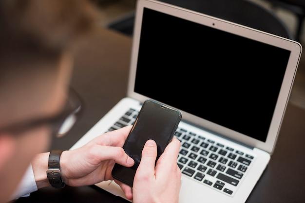 De hand die van een zakenman de mobiele telefoon voor laptop met behulp van