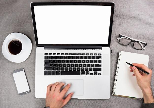 De hand die van een zakenman digitale tablet gebruiken die op spiraalvormige blocnote over het grijze bureau schrijven