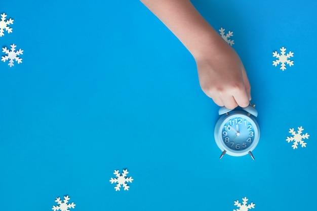De hand die van het kind blauwe wekker houdt die vijf tot twaalf met document sneeuwvlokken toont