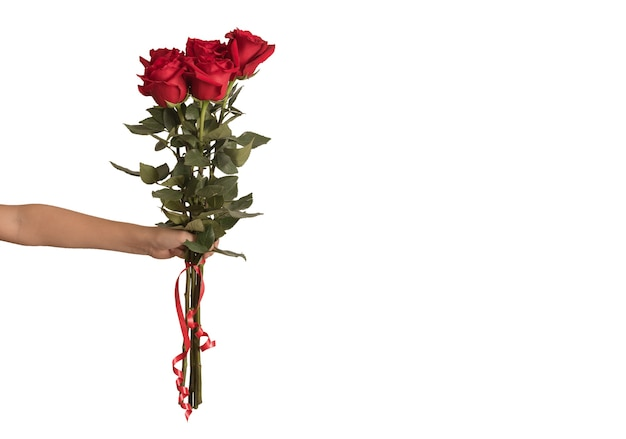 De hand die van het kind een boeket van rode rozen voor geïsoleerde vakantie en viering houdt