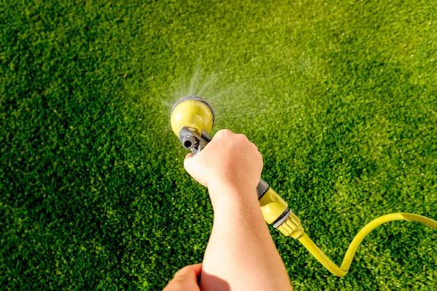 De hand die van het kind het gras tijdens de zomer met een slang water geeft.