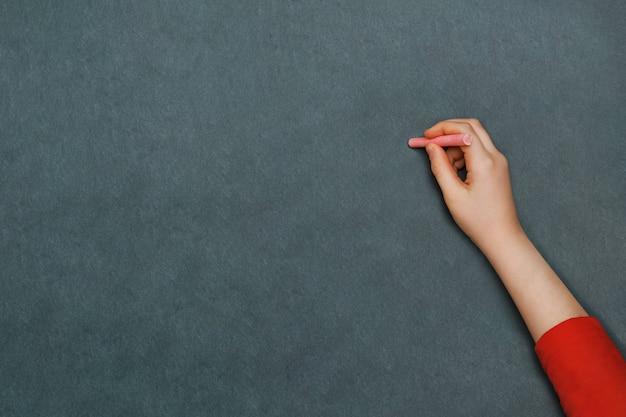 De hand die van het kind met krijt schrijft.