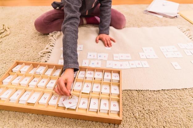 De hand die van het studentenmeisje kaarten met brieven gebruiken om woorden te schrijven, die op de klaslokaalvloer zitten van haar montessorischool.
