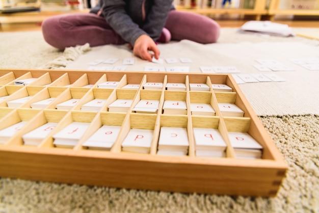 De hand die van het studentenmeisje kaarten met brieven gebruiken om woorden te vormen