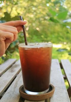 De hand die van het wijfje een stro in bevroren koffieglas met vaag groen gebladerte op achtergrond houdt
