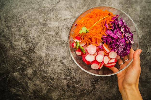 De hand die van het wijfje verse salade in kom over grungeachtergrond houdt