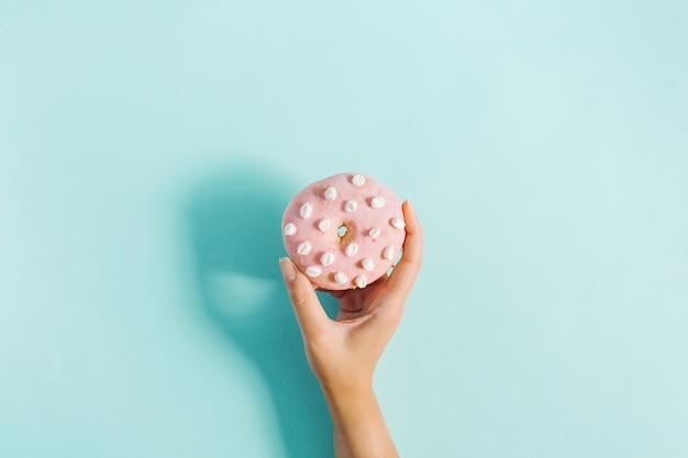 De hand die van vrouwen doughnut op blauw houdt