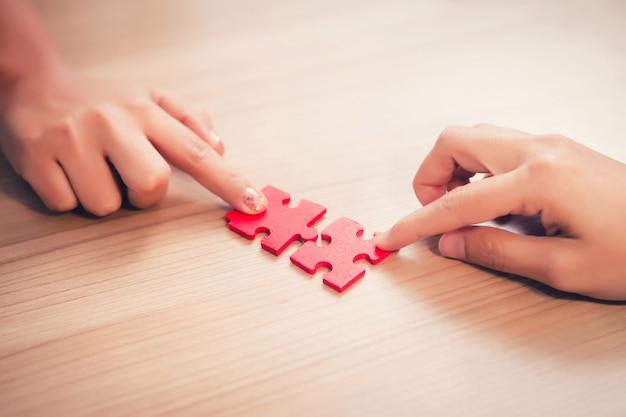 De hand die van vrouwen puzzelstukken in bureau houden