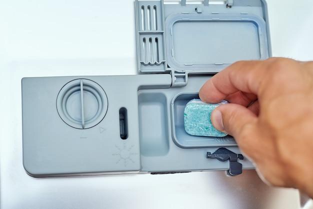 De hand die zeeptablet in de afwasmachinemachine zetten, sluit omhoog. keuken huishoudapparaat concept